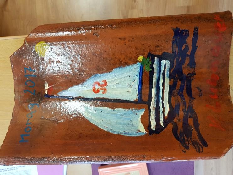Obrazek łódki namalowany na dachówce przez Katarzynę Lubnaue